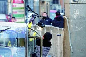 一名男子站在打开车门的空摩的旁,举起小黄车砸到路边。龚先生供图