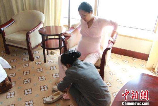 月子会所内,一名月嫂正在照顾孕妇的起居。钟升摄