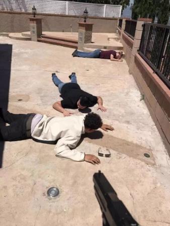 屋主张岩用枪将三名窃贼制伏趴在地上。(美国《世界日报》)