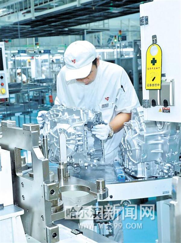 哈尔滨东安汽车发动机制造有限公司,工人正在装配自动变速箱.