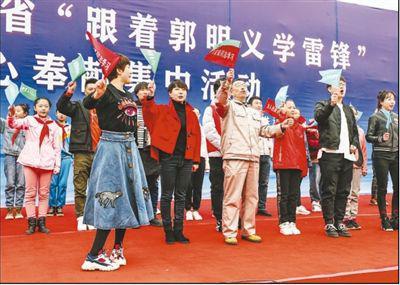 """在葫芦岛市文化广场举行的辽宁省""""跟着郭明义学雷锋""""爱心奉献集中活动现场,郭明义(前排中)与志愿者合唱《学习雷锋好榜样》。新华社记者 潘昱龙摄"""